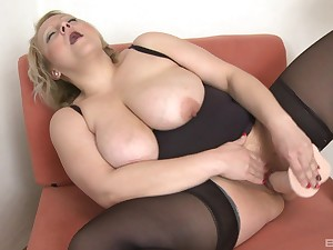 Chubby mature works her pussy just about a stiff toy cock